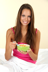 young beautiful woman with bowl of cornflakes in bed