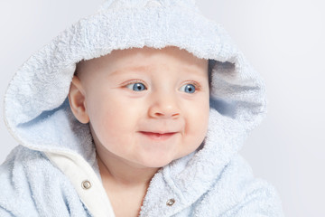 portrait of a cheerful child in blue bathrobe