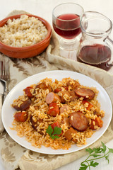 rice with chorizo and sausages on the plate and glass of wine