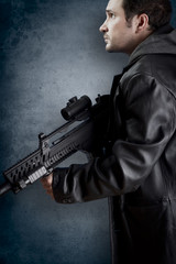 Man with long leather jacket and assault rifle