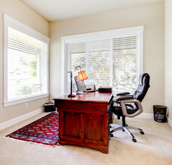Home office with mahogany desk and letaher chair.