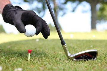 Zelfklevend Fotobehang Golf Closeup of a man placing a golf ball on the tee