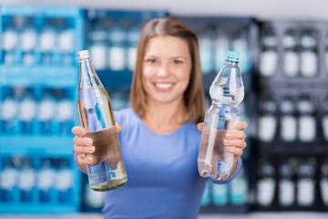 frau zeigt glasflasche und plastikflasche