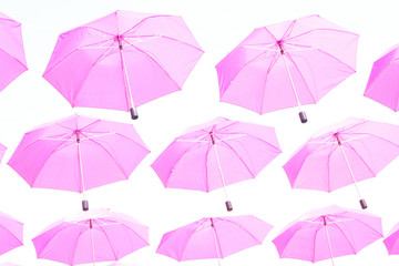 Pink umbrellas flying in the sky