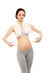 A sportive young woman with a towel, pointing at her belly