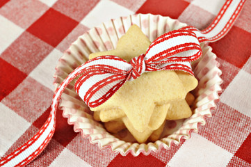 Star cookies with ribbon on  checkered cloth