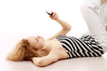 A smiling girl lying on the floor with a mobile phone
