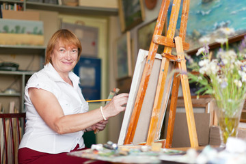 Female artist paints anything on canvas