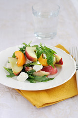 Summer fruit and goat cheese salad on a plate