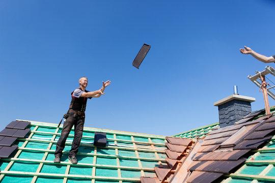 zwei dachdecker werfen dachziegel