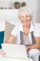 lächelnde seniorin mit laptop auf dem sofa