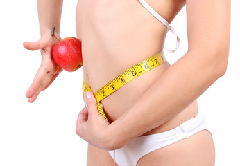 closeup of woman measuring her waist and holding an apple