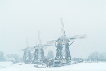Three Dutch windmills during snowfall