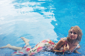 Young blonde woman in the swimming pool, fashion portrait.