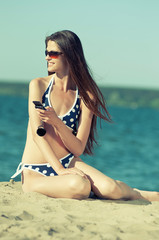 woman talking by phone on a beach