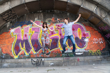 Couple jumping off the ledge with graffiti background