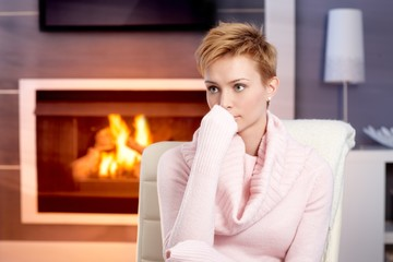 Attractive woman sitting by fireplace at home