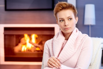 Beautiful woman thinking by fireplace