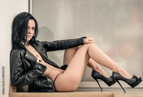 Sexy girl wearing high heels shoes and leather jacket indoors ...
