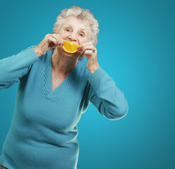 portrait of senior woman holding a orange slice in front of her