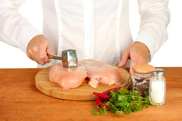 Chef beats meat on wooden table