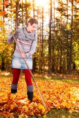 Attraktive Frau beim Harken von Herbstlaub