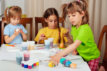 Three little girls (sisters) painting on Easter eggs