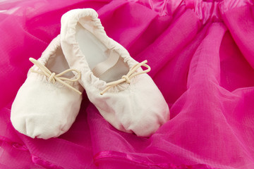 Ballet shoes of a girl on pink background