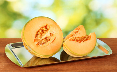 Cut melon on metal tray on green background close-up