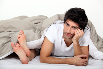 Annoyed man lying next to a woman in bed