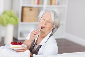 seniorin genießt ein stück kuchen