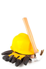 Hammer leaning against hard hat and builder's gloves