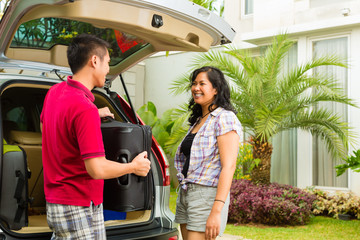 Asian couple packing car with suitcases for holiday