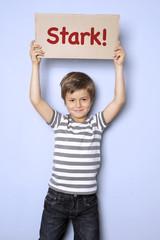 """Kind hält Schild auf dem """"Stark"""" steht"""