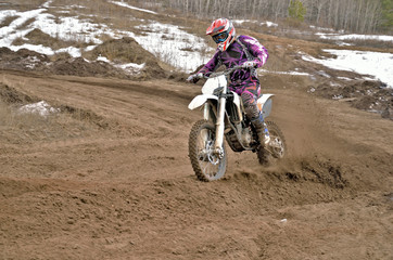 Motocross rider on a motorcycle rides cornering