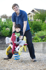 Father helping disabled son play at playground