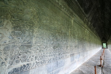 Long wall full of bas reliefs at the Angkor Wat temple