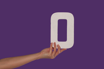 Female hand holding up the number 0 from the left