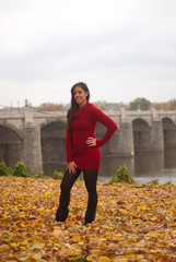 Young lady in red standing on leaves in front of bridge