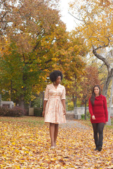 Two lady friends walking on leaf covered path towards camera