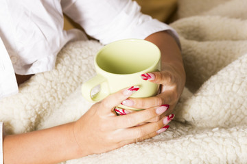 Female hands over blanket with cup of tea