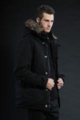 Handsome man dark winter fashion. Studio shot. Wearing hoody..