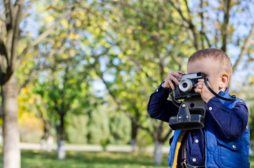 Young boy taking a photograph