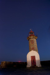 Lighthouse at night with stars on the sky
