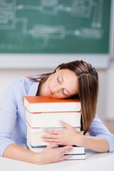 studentin schläft auf einem stapel bücher
