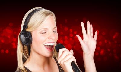 frau singt mit geschlossenen augen vor rotem Hintergrund