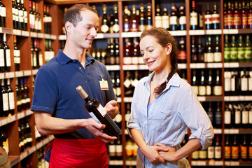 Sommelier zeigt Frau eine Weinflasche