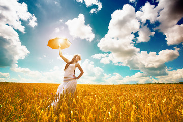 woman with umbrella is enjoys summer day in the field
