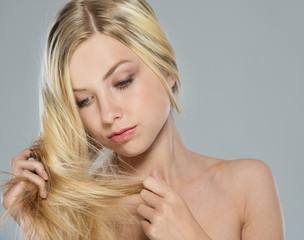 Portrait of blond girl checking hair ends
