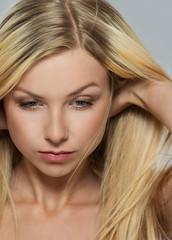 Portrait of blond girl tweaking hair